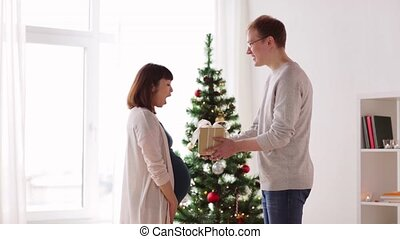 husband giving christmas present to pregnant wife -...