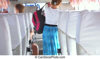 Interior of bus with passengers seated in places in slow...