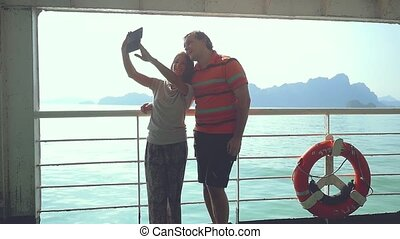 Happy funny couple takes selfie with smartphone while...