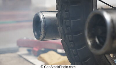 Close up of old motorbike exhaust pipe releasing fumes in...