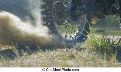Wheel of motocross bike starting to spin and kicking up...