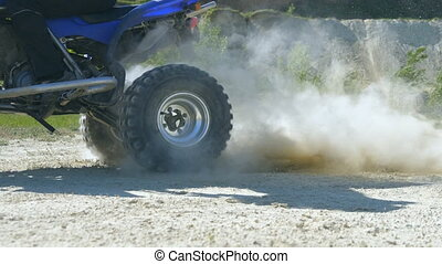 Wheel of ATV starting to spin and kicking up ground or dirt....