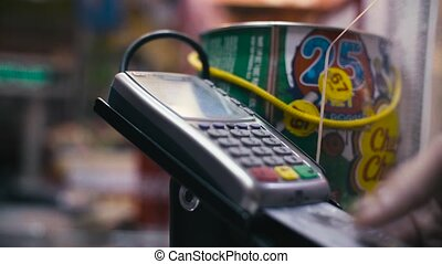 Man's hand inserting card in card payment terminal and...