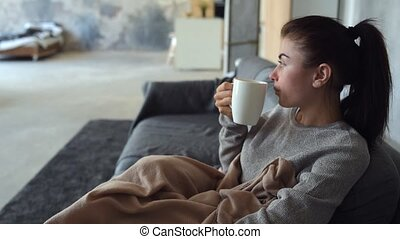 Exhausted brunette enjoying her cup of aromatic tea -...