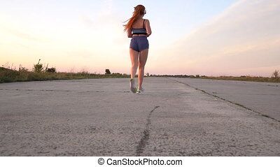 woman running and listening to music on headphones, back...