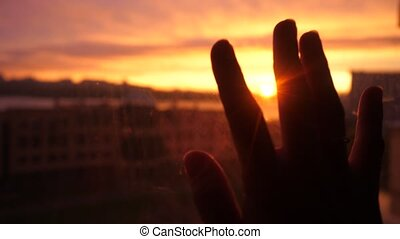 Women hand touches the sun by the window on sunset city...