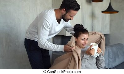 Loving millennial man covering ill wife with blanket -...