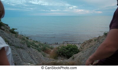 Young woman and man go to sea shore on summer evening...