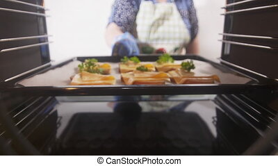 Woman placing cheese toasts on a baking sheet into the oven
