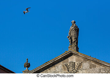 Ancient statue on the roof of one of houses in the centre of...