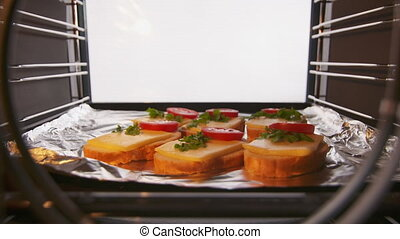 Home kitchen oven interior. Cheese and tomato toasts baked...