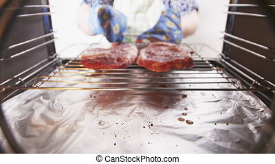 Woman placing grilling rack with two raw beef marbled steaks...