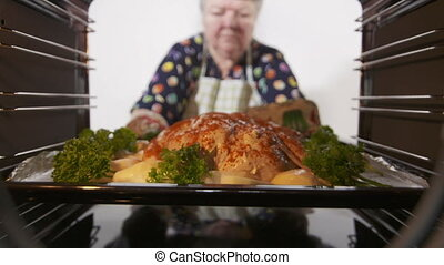 Making whole roasted chicken with potatoes baked in the...