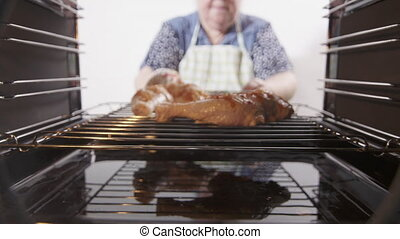 Making roasted broiled chicken legs baked in the oven. Woman...