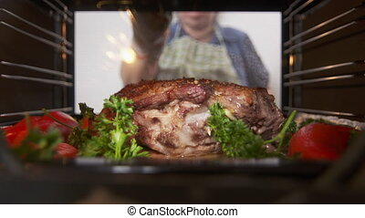 Cooking roasted pork neck with vegetables and herbs baked in...