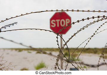 Red stop sign behind safety fence of barbed wire - Red stop...