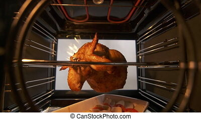Cooking roasted whole chicken on the rotisserie spit in hot...