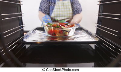 Cooking roasted vegetables in hot convection oven. Woman...