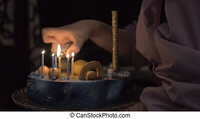 Lighting the candles on birthday cake - Slow motion shot of...