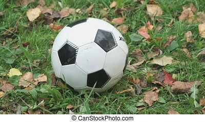 Little boy hits his foot on a soccer ball outdoors -...