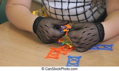 Little girl plays in kindergarten indoors. Close-up of hands...