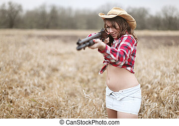 Sexy woman hunting with a shotgun.
