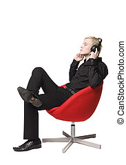 Man siting in armchair listens to music