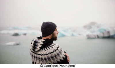 Young bearded man standing in Jokulsalon ice lagoon and...