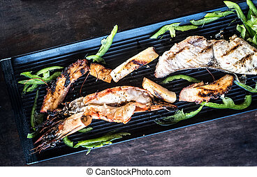 appetizing grilled seafood on black plate - appetizing...