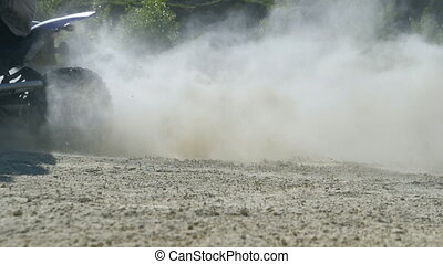Biker on ATV enters the turn at high speed, kicking up dirt...