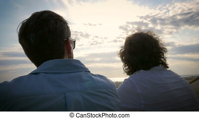 Handheld of two men sitting together watching the sunset -...