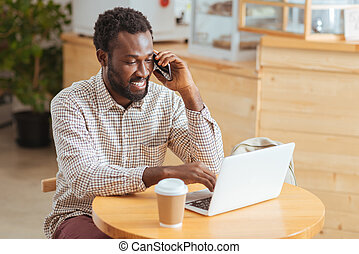 Cheerful young man discussing work issues in cafe -...
