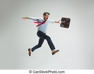 Businessman running with a briefcase, isolated on gray...