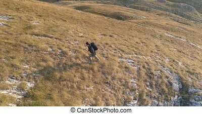 Hiker climbing the mountain slopes, aerial