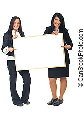 Two businesswomen with blank placard - Full length of two...