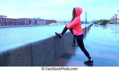 Young mixed race athletic female runner warming up before...