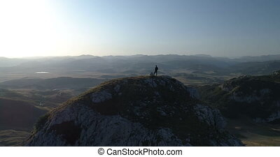 man stands on top of a mountain, aerial