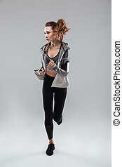 Full length image of a young sports woman running in studio...
