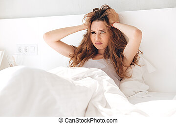 Annoyed woman holding her head in bed