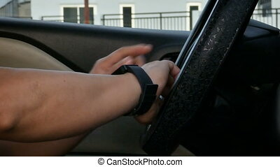 Close up shot hands of man using smart watch in the car