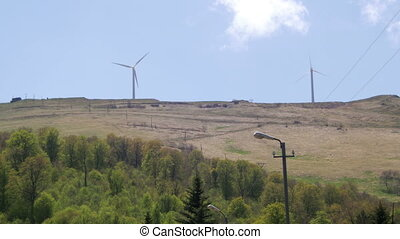 Wind farm in the mountains. Summer, The blades rotate from...
