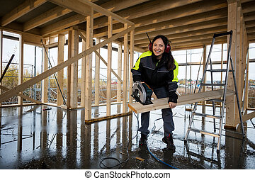 Happy Female Carpenter Cutting Wood With Electric Saw At...