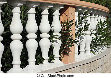 a white baluster with wall in nature