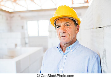 Senior architect or civil engineer on the construction site....