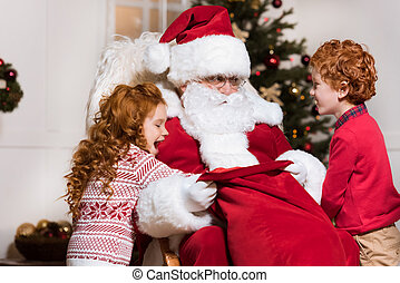 kids looking for gifts in santas bag - portrait of happy...