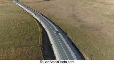 aerial view of a luxury car driving on country road on a...
