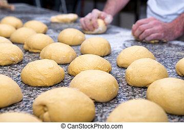 the baker prepares bread dough
