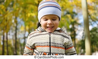 Child in autumn Park having fun playing and laughing , walking in the fresh air