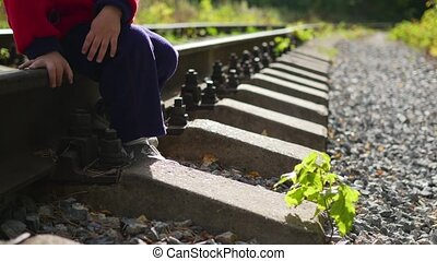 A lonely boy sitting on the railroad tracks. Dangerous games...