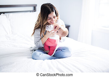 Mother and baby child on a white bed. - A Mother and baby...